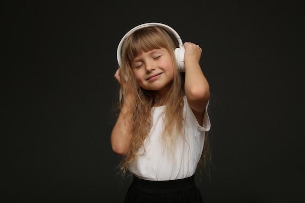 Девочка-ребенок наслаждается музыкой в своих больших белых наушниках и улыбается.