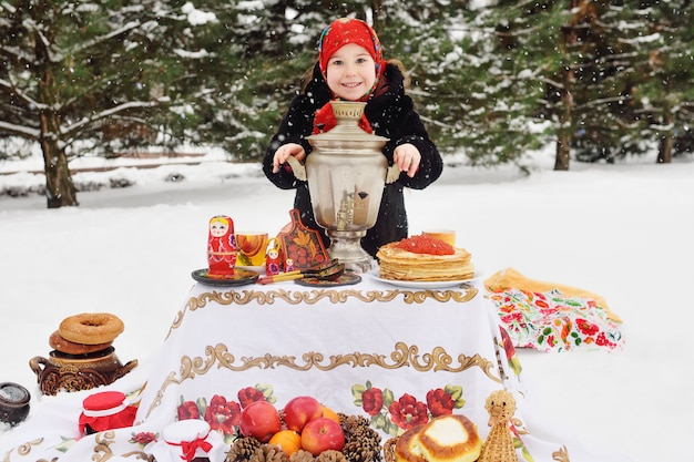 Child girl in a fur coat and in a scarf in russian style holding a large samovar in the hands