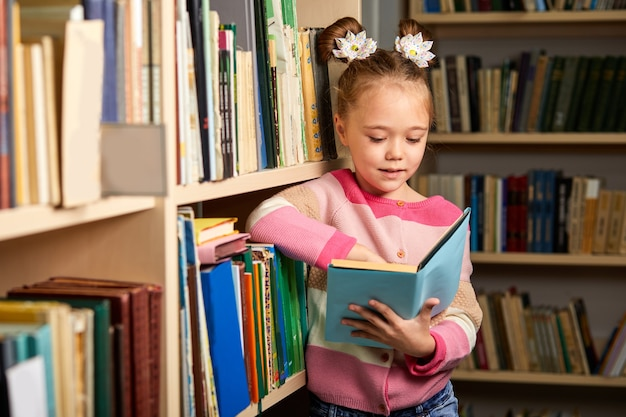 Child girl get carried away by reading a book in library, standing betweel multi coloured bookshelves