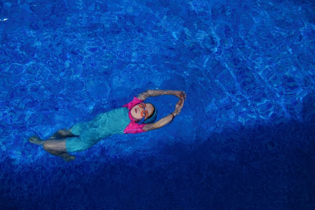 Child girl in goggles swimsuit and cap is training swimming in pool