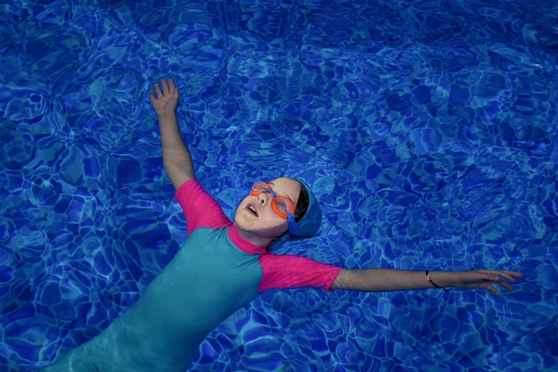 Child girl in goggles, swimsuit and cap lying calmly on back, copyspace
