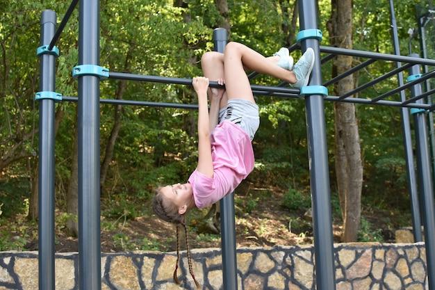 子供の女の子は屋外の鉄棒に掛かっています。体操スティックで陽気な女の子アスリート