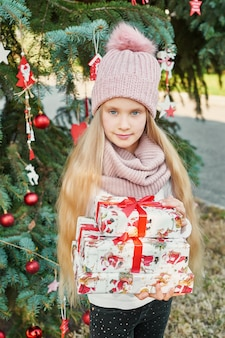 Child girl in a hat and scarf near the christmas tree