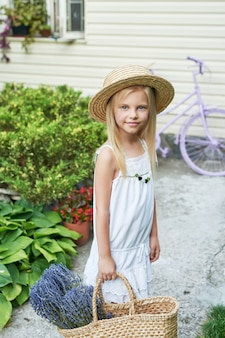 Child girl in hat with a basket of lavender in the garden in summer