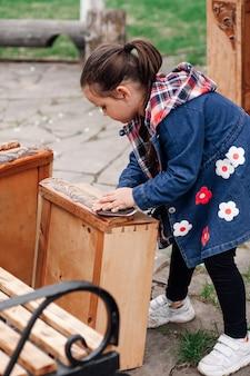 Маленькая девочка помогает родителям полировать старый деревянный комод для ремонта и повторного использования на спине ...