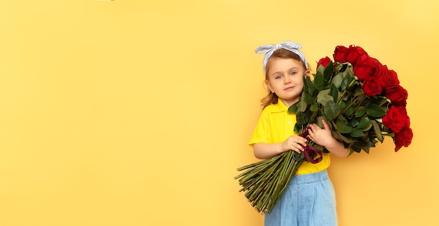 子供の女の子は黄色の壁に分離された赤いバラの花の大きな花束を保持します。