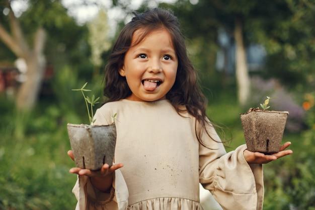 地面に植える準備ができている苗を保持している子供の女の子。茶色のドレスを着た小さな庭師。