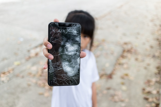 Child girl holding a broken smartphone and broken touch screen on hand
