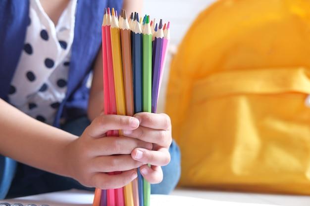 多くの色鉛筆を持っている子供の女の子