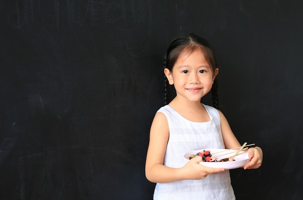 Child girl holding plate of homemade chocolate donuts against blackboard background.