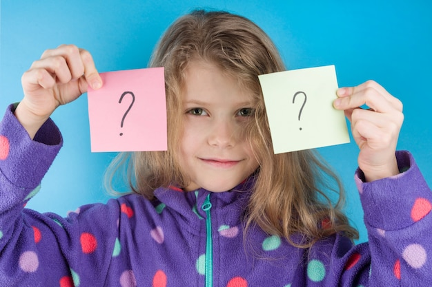 Child girl holding stickers with question marks
