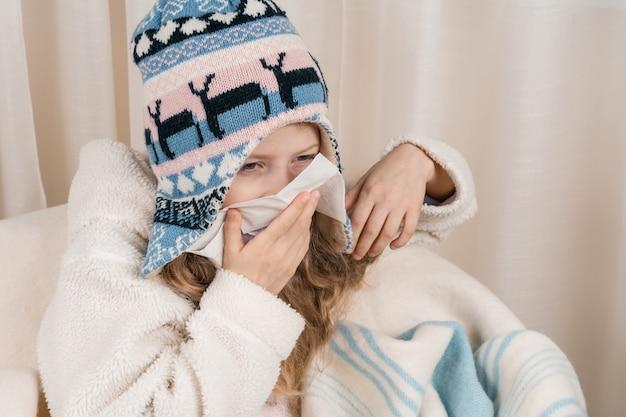Child girl at home sneezes in handkerchief