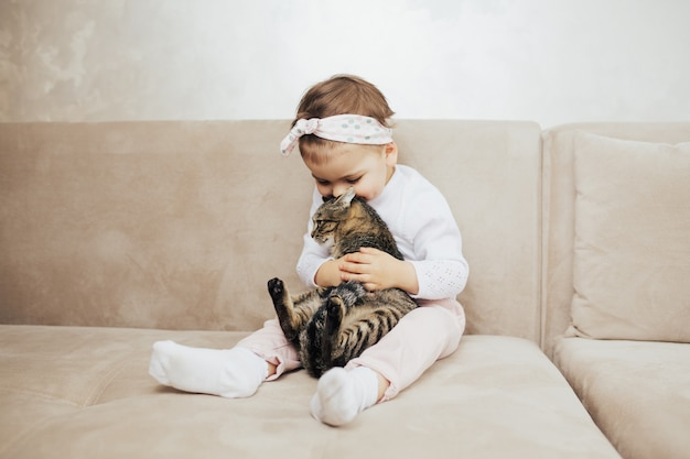 子供の女の子は優しさと愛で彼のかわいい面白い猫を抱きしめてキスします