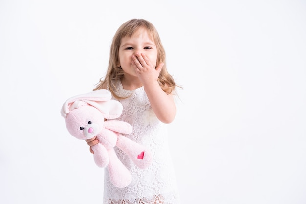 Child girl hugging her pink teddy bunny sending a kiss on white wall