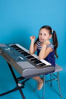 파란 드레스에 아이 소녀는 의자에 앉아 그녀의 팔꿈치로 피아노를 연주