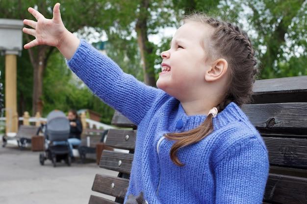 Ребенок девочка в синем вязаном свитере ест мороженое, сидя на скамейке.