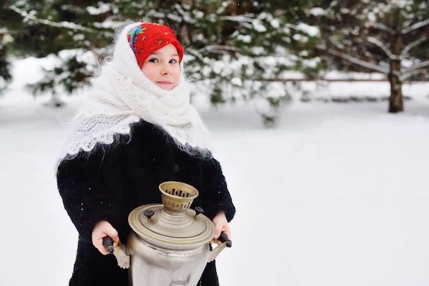 Девочка в шубе и платке по-русски держит большой самовар из снега и леса