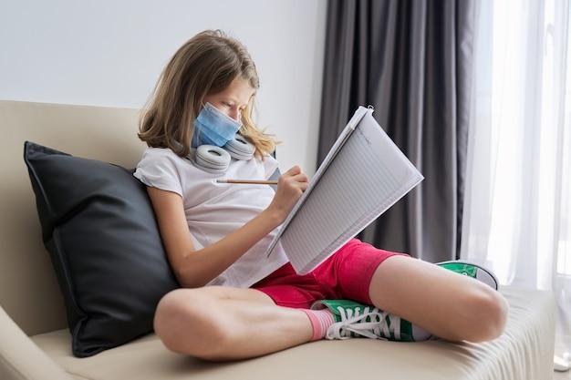 自宅のソファに座っている医療用保護フェイスマスクの女児、学校のノートで勉強している学生