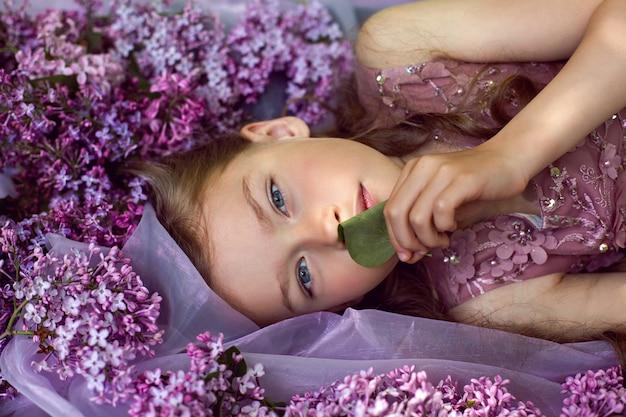 Девочка в фиолетовом цветочном платье лежит на земле среди сирени на вуали весной