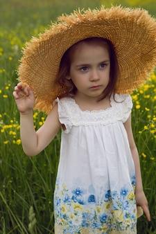 밀짚 모자에있는 아이 소녀와 꽃과 드레스는 노란색 필드에 서