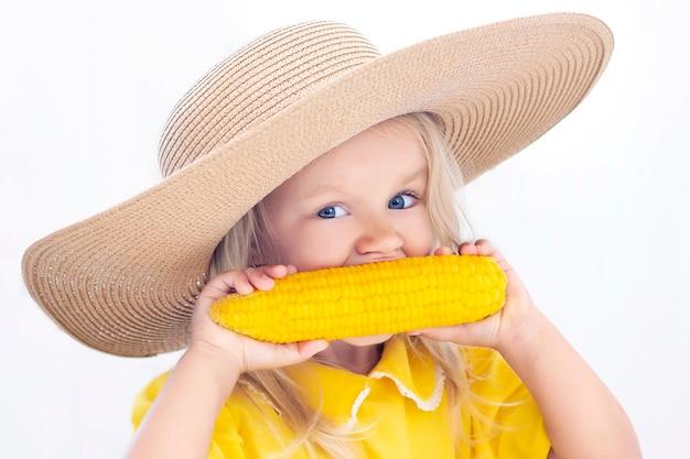 Ребенок девочка в соломенной шляпе в желтой одежде ест кукурузу