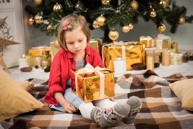 Ребенок девочка в ожидании открытия золотой коробки подарков на рождество