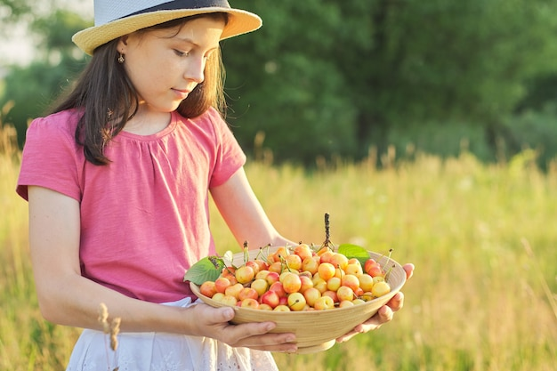 黄色の甘い果物のボウルと帽子の子女の子
