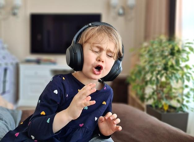Ребенок девочка в наушниках эмоционально поет песню дома