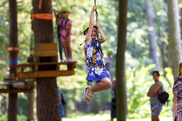 Девушка ребенка в ремнях безопасности и шлеме на пути веревочки.
