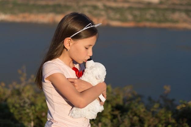 子供の女の子はぬいぐるみクマを抱きしめています