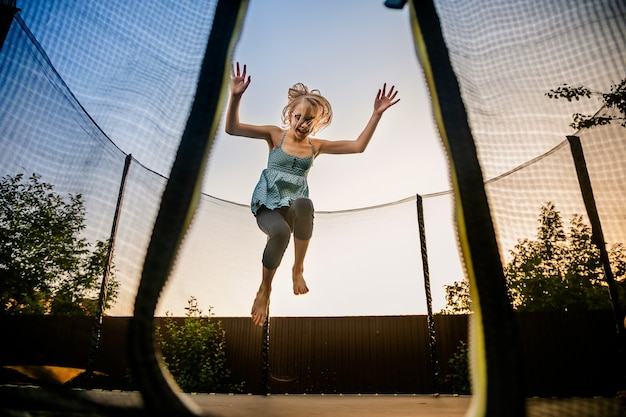 Child girl jumping high on big trampoline outside in garden on summer sunset