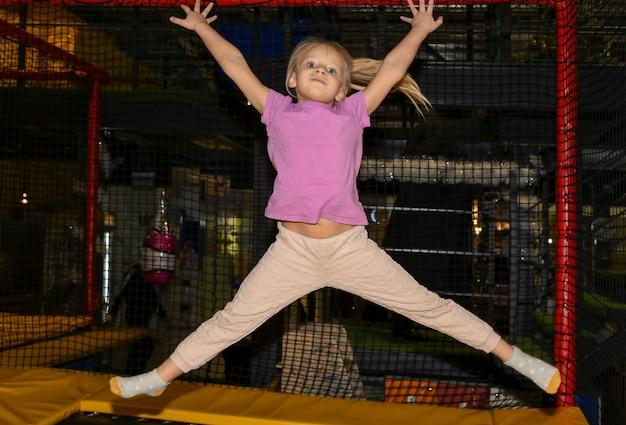 Детская девочка прыгает на батуте в игровом центре.