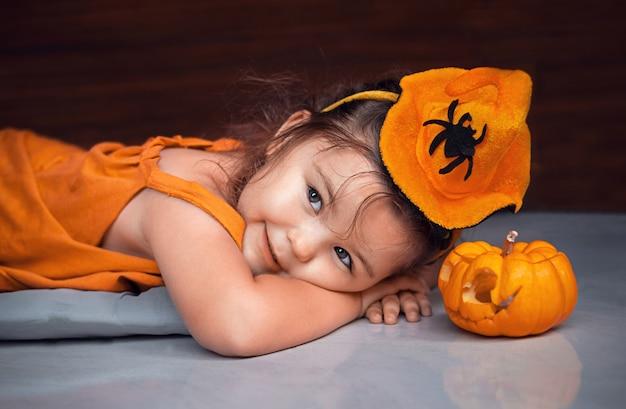 子供の女の子はハロウィーンの装飾ジャック-o-ランタンの隣の床にあります