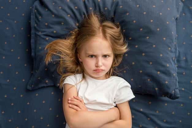 Child girl lying on the bed refuses to sleep