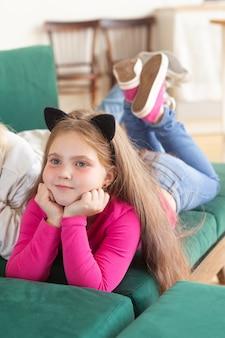 그녀의 머리 검은 고양이 귀에 소파에 누워 어린 소녀 어린 시절과 카니발 개념