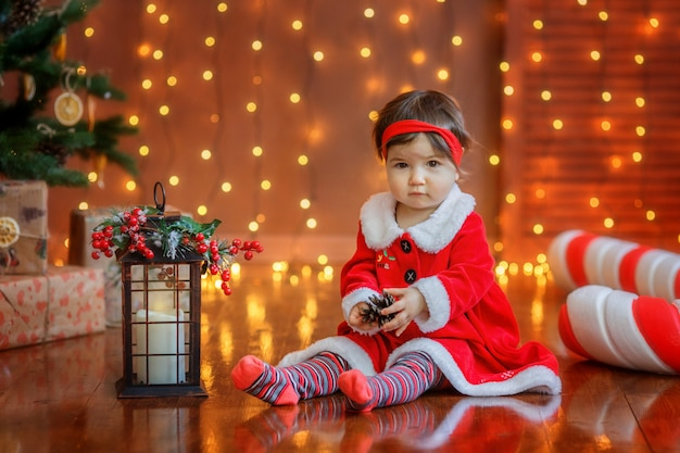 Child girl near the christmas tree in the photo studio