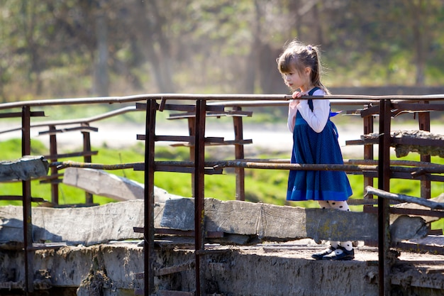 Child girl in nice blue dress stands alone on a bridge.