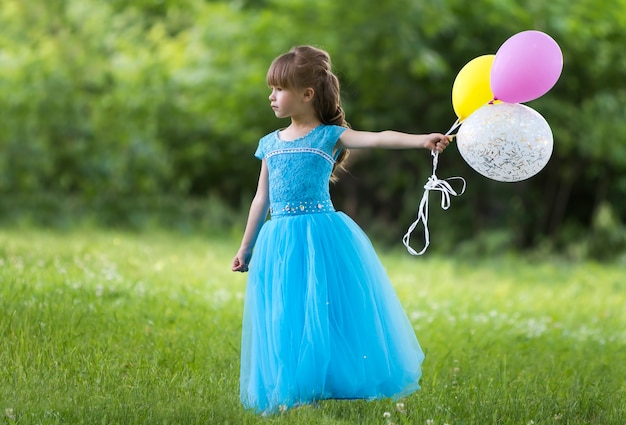 Child girl in nice long blue evening dress holds colorful balloons.