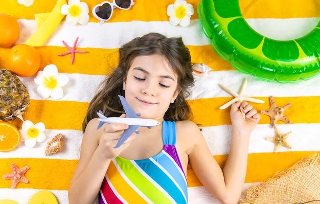 飛行機と海のビーチタオルで子供の女の子。セレクティブフォーカス。キッド、