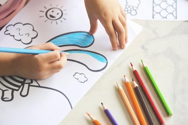 Ребенок девочка рисует на листе бумаги цветными карандашами