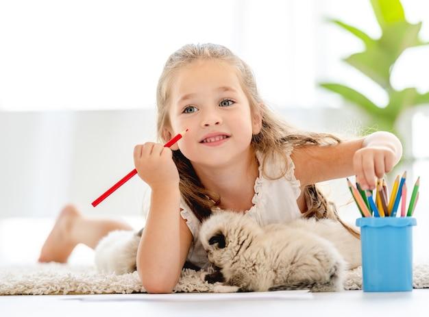 Девушка ребенка рисует с котятами тряпичной куклы на полу и думает. маленькая женщина рисует красочными карандашами и домашних животных котенка рядом с ней дома