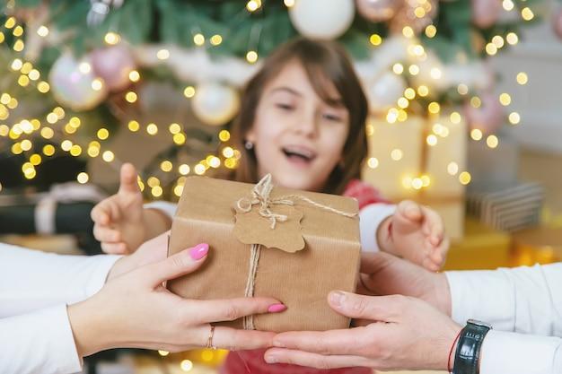 Родители ребенка девочки дарят подарки на рождество. выборочный фокус. праздничный день.