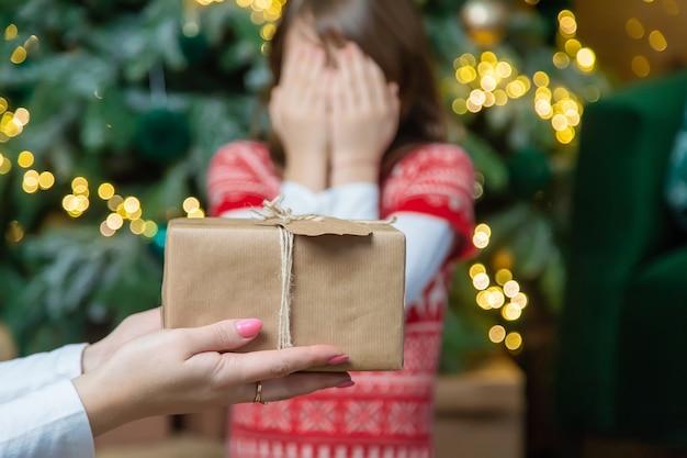 子供の女の子の両親はクリスマスにプレゼントを贈ります。セレクティブフォーカス。ホリデー。
