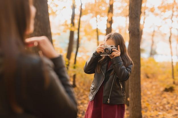 어린 소녀 사진 작가는 가을에 공원에서 어머니의 사진을 찍습니다. 취미, 사진 예술 및 여가 개념.