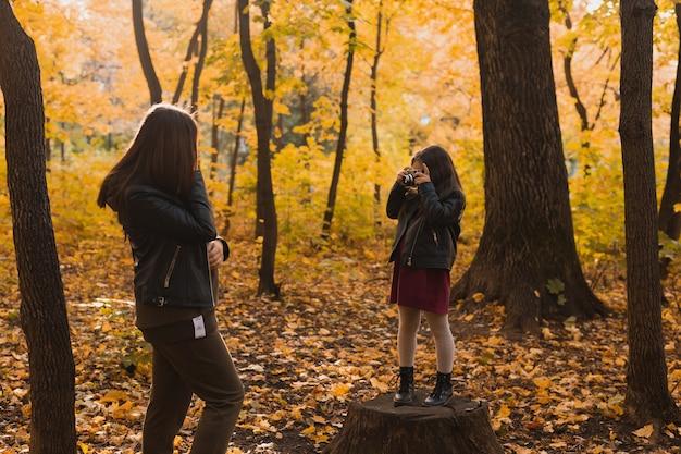 子供の女の子の写真家は、秋の趣味の写真アートと公園で母親の写真を撮ります