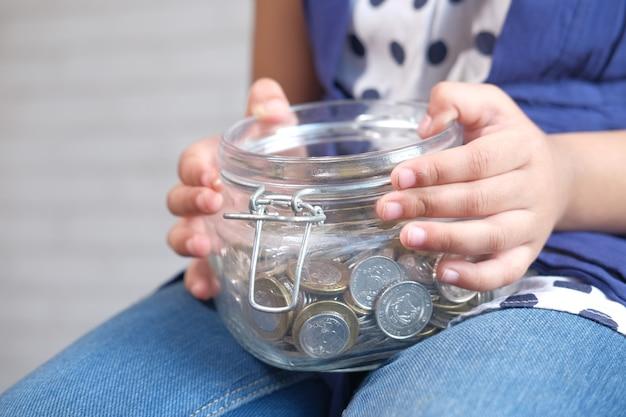 저장을위한 자식 소녀 더미 동전을 닫습니다.