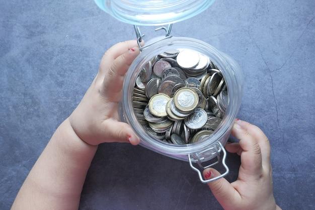 Ребенок девочка куча монеты для экономии, вид сверху