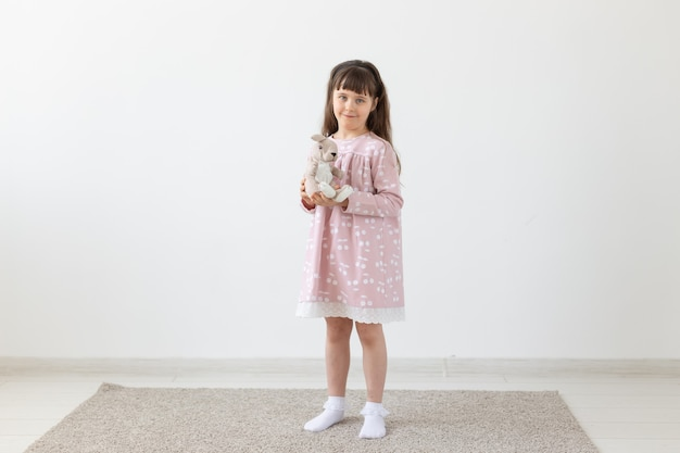Child girl in pink dress with toy in white room