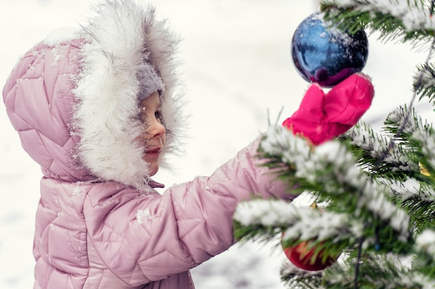 Child girl in a pink warm coat and a hood is happy by the christmas tree outdoors. new year and christmas concept