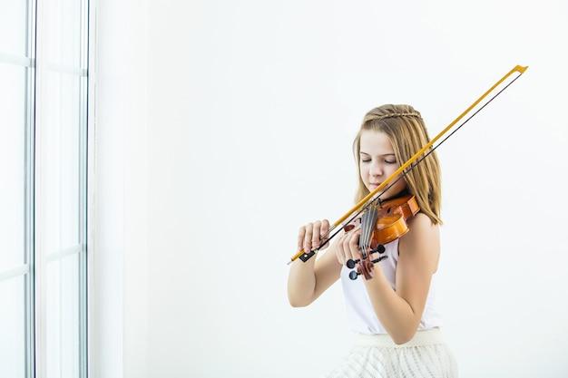 Маленькая девочка играет на скрипке, чтобы учиться красивой и счастливой в белой комнате с окном
